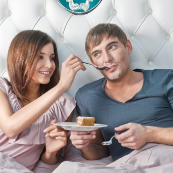 Young lively couple eacting cake in their bed