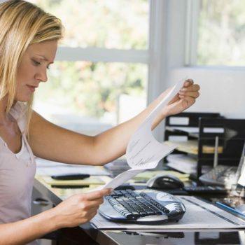 Mujer-en-su-oficina-de-casa-frente-a-un-ordenador-revisando-unos-papeles