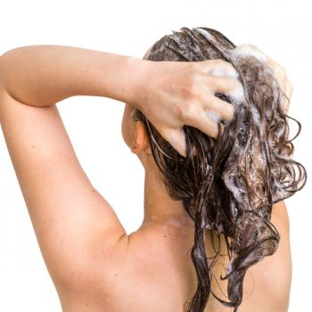 Attractive woman washing hair with shampoo in shower - isolated on white background